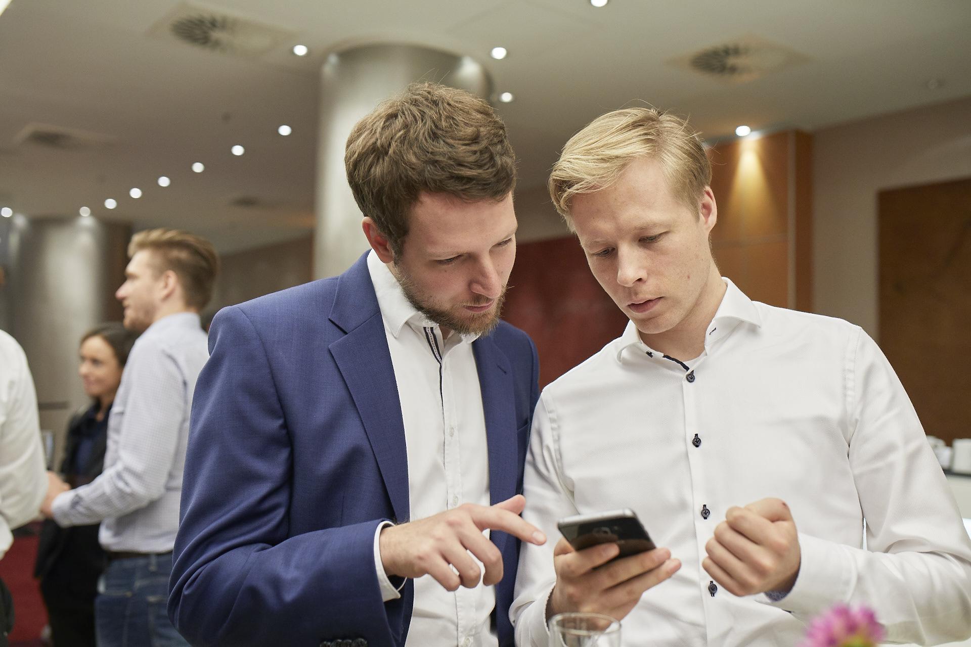Geschäftsmann zeigt seinem Partner etwas auf seinem Handy an einer Konferenz