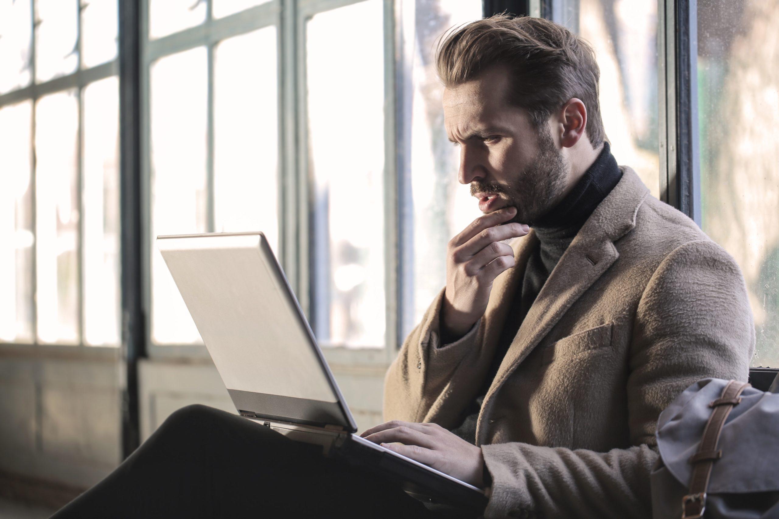 Mann guckt verwundert auf sein Laptop