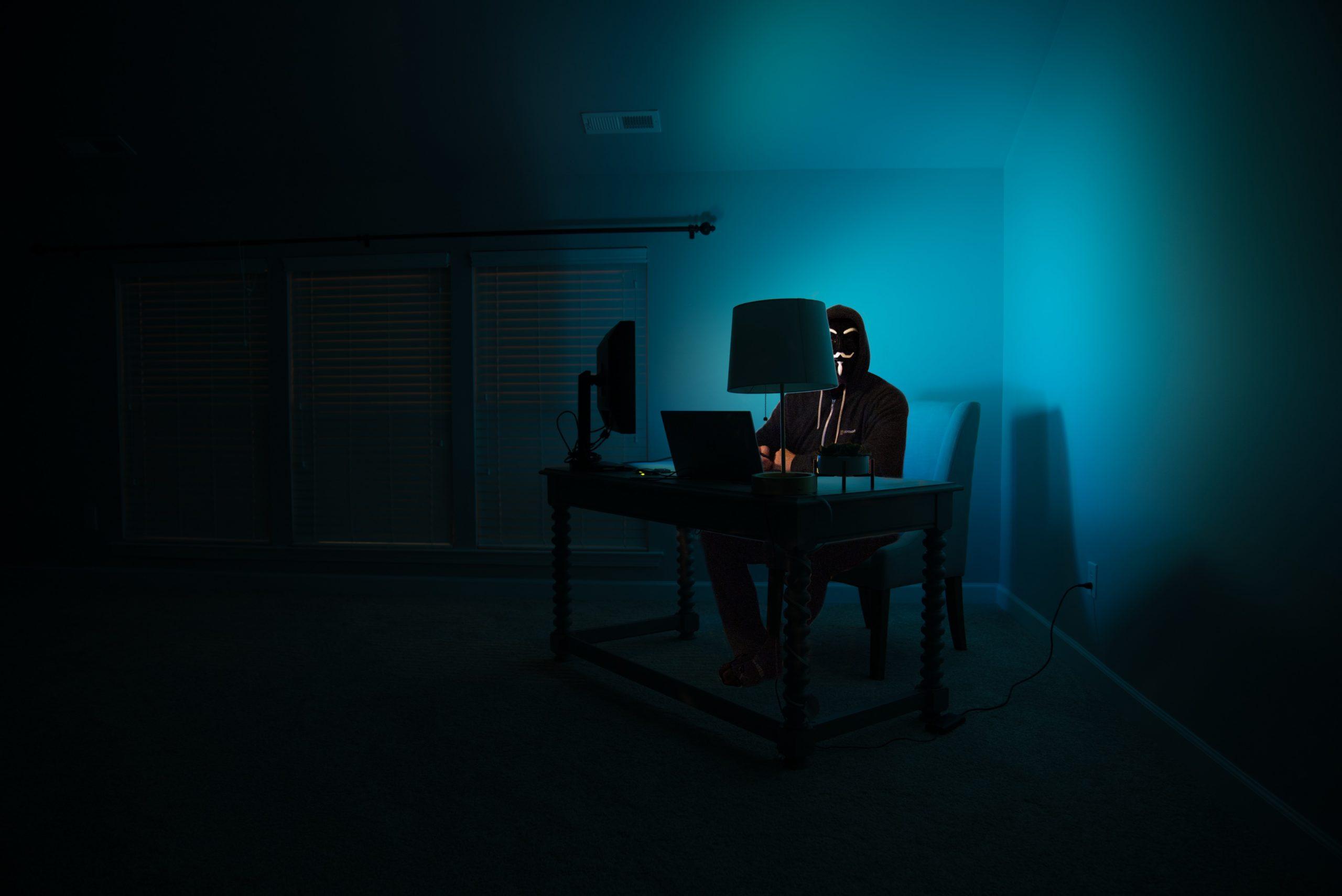 Anonyme Person sitzt im dunklen Raum auf seinem Laptop