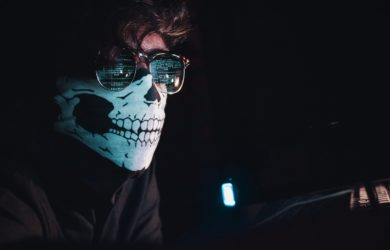 Mann mit einer Maske und Sonnebrille sitzt im dunklen Raum und kodiert