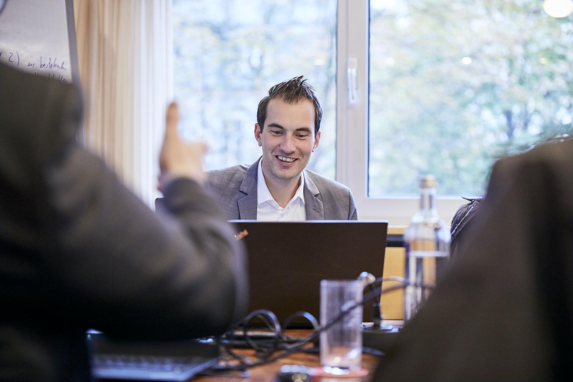 Mann sitzt bei einer Konferenz hinter seinem Laptop