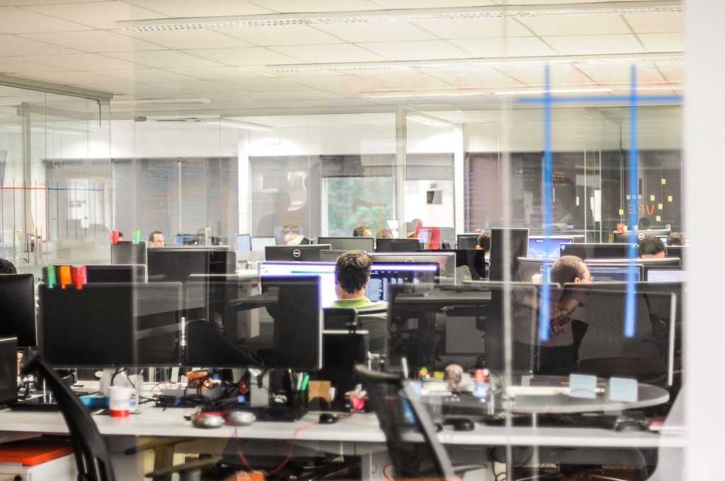 Arbeiter im Büro voller Monitore