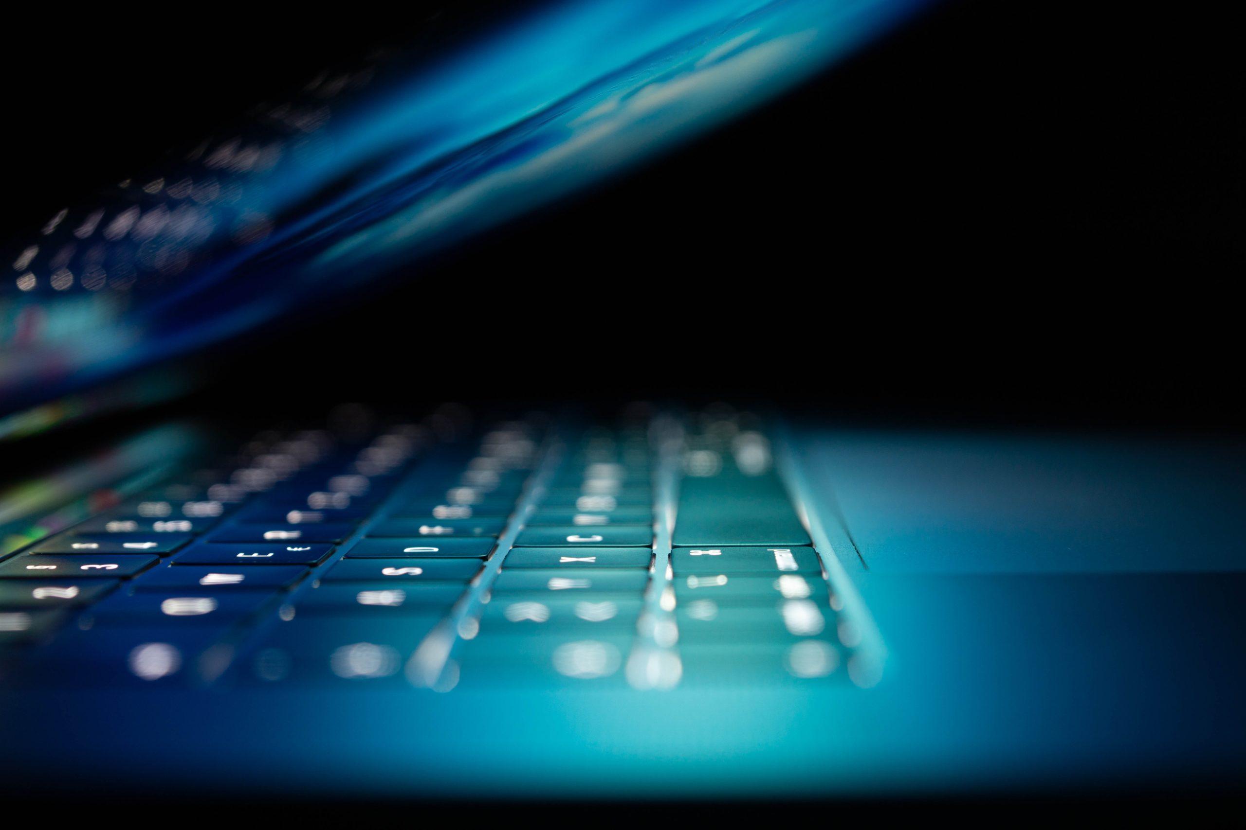 Halbwegs zugeklapter Laptop im dunklen Raum