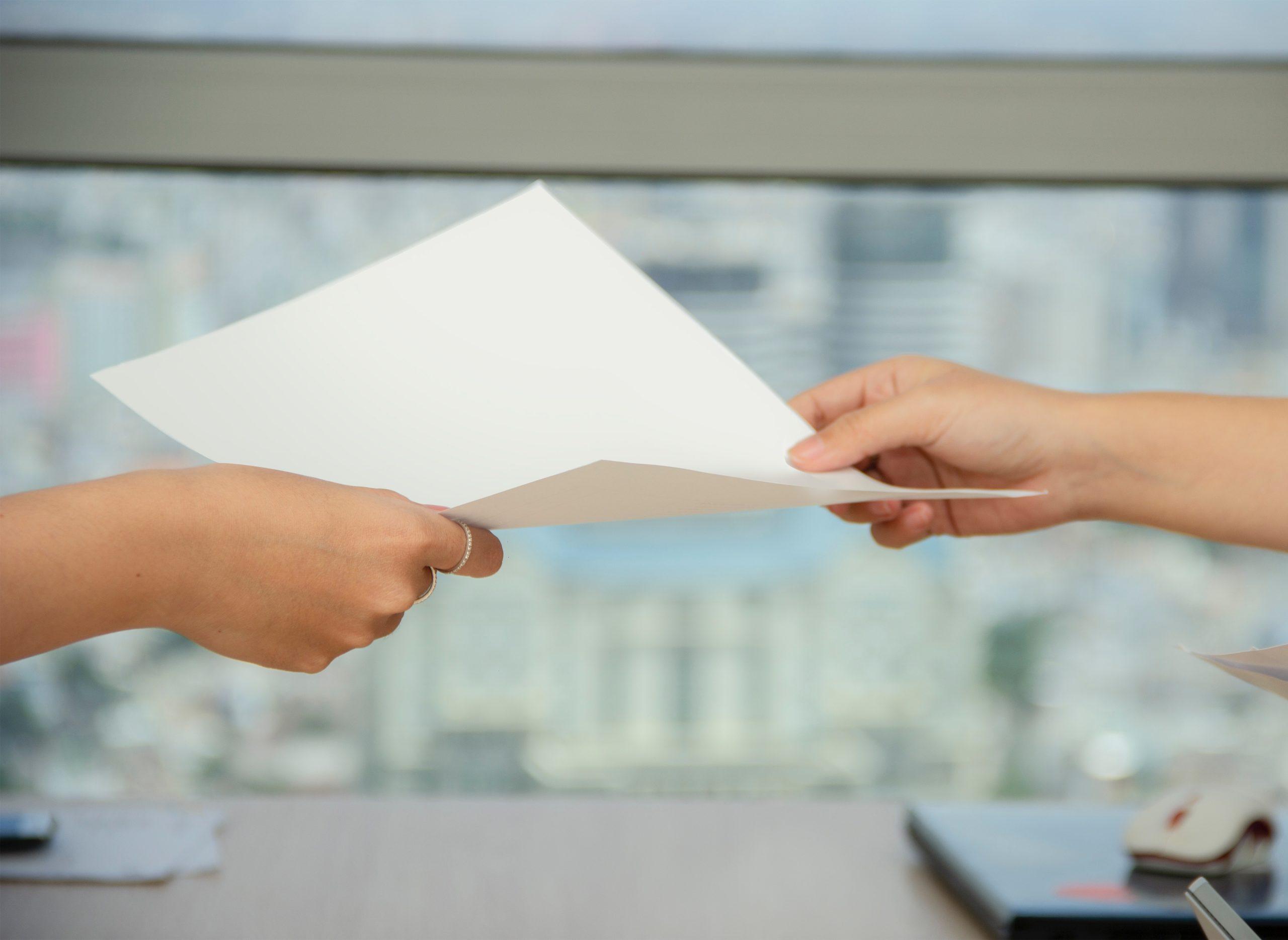 Person gibt einer anderen Person Papier