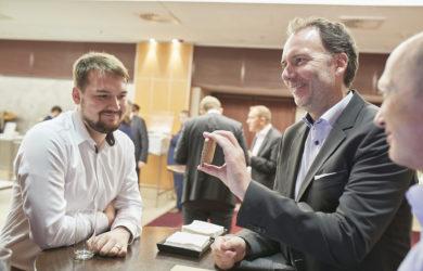Geschäftsmann zeigt anderen Männern etwas auf seinem Handy auf einer Konferenz