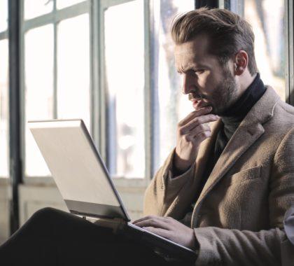 Mann gukct verwirrt auf sein Laptop
