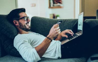 Mann sitzt auf dem Sofa und bestellt Sachen online auf dem laptop