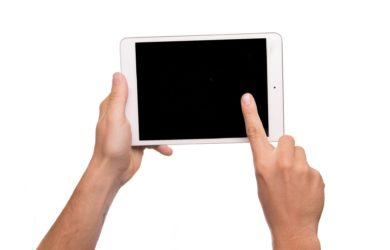 Mensch zeigt auf Tablet Bildschirm