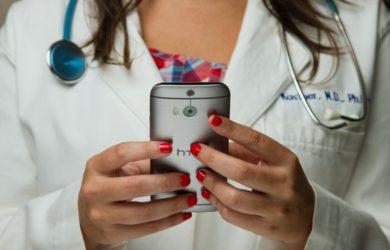 Ärztin hält ein Handy in den händen