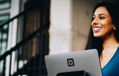 Frau mit Laptop lächelt