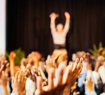Alle Zuhörer strecken ihre Hände hoch um Moderator auf der Bühne nachzmachen