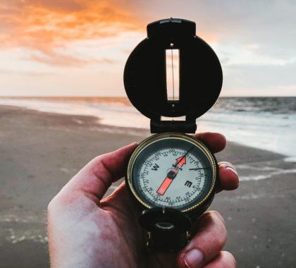 Mann hält Kompass mit Strand im Hintergrund