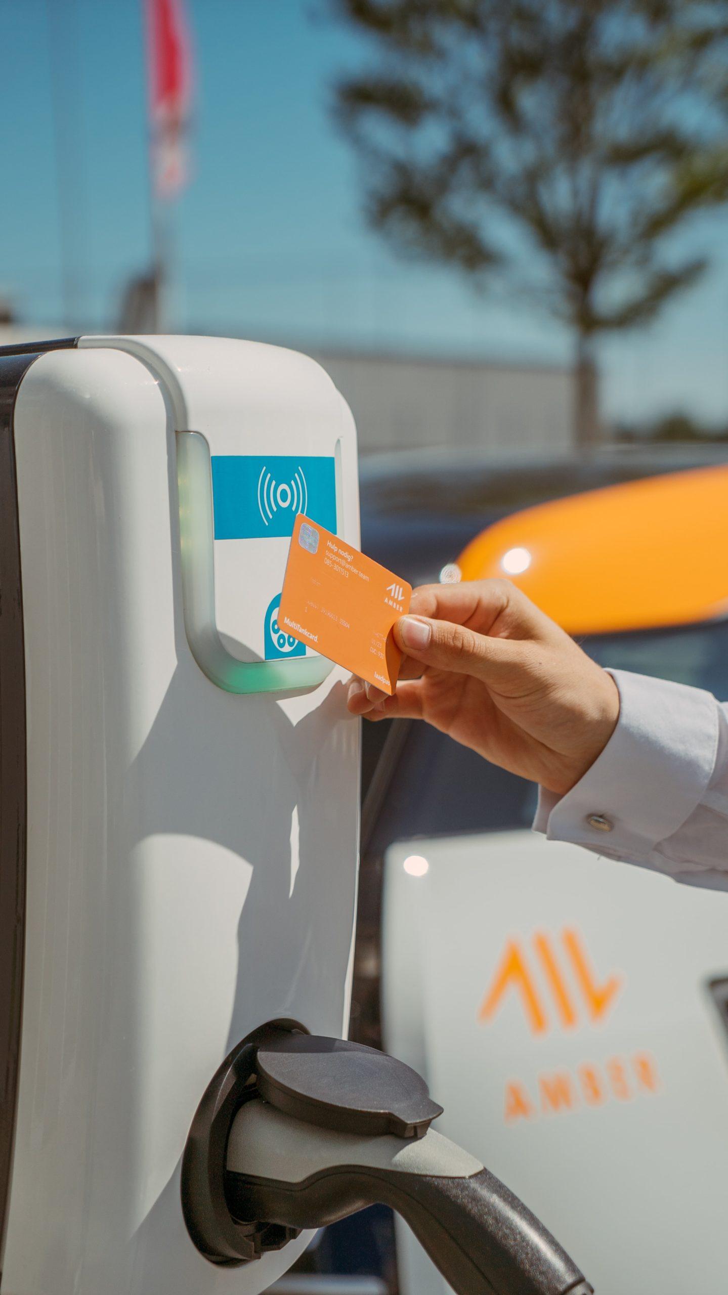 Person bezahlt mit Bezahlkarte an der Ladesäule für E-Auto