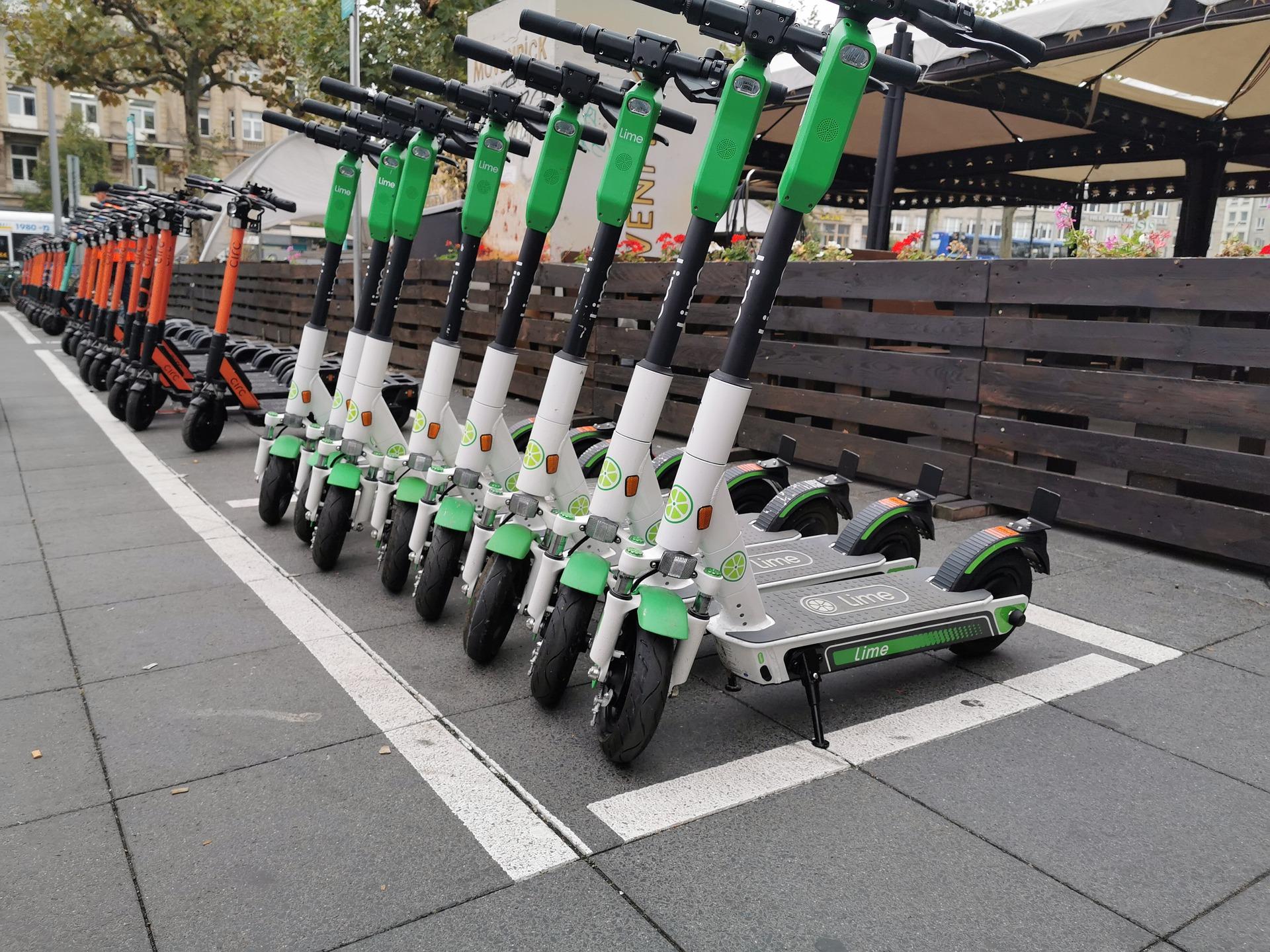 Lime E-Scooter stehen nebeneinander auf der Straße