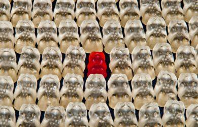 Viele weiße Gummibärchen und ein rotes Gummibärchen