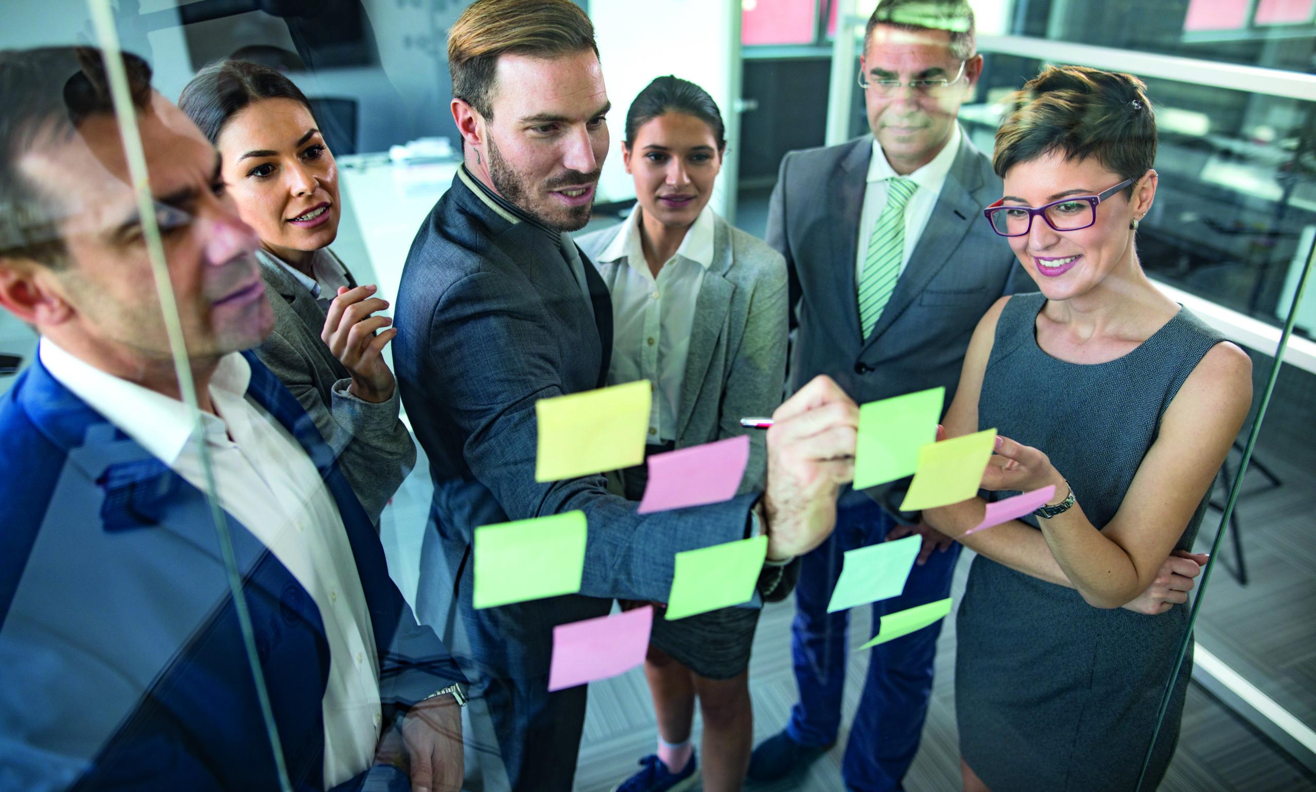Eine Gruppe von Geschäftsleuten gemischten Alters sitzt im Büro und arbeitet an innovativen Geschäftsideen.