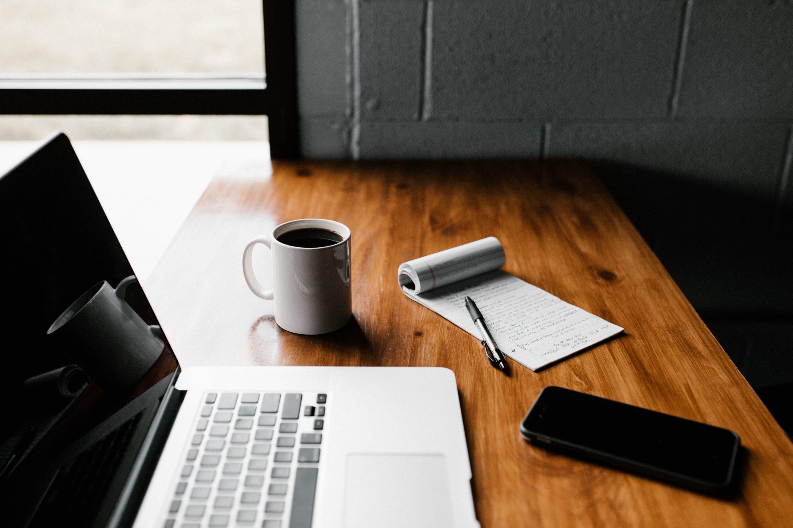 Home office Tisch mit Laptop, Cafe, Handy und Nozizenbuch