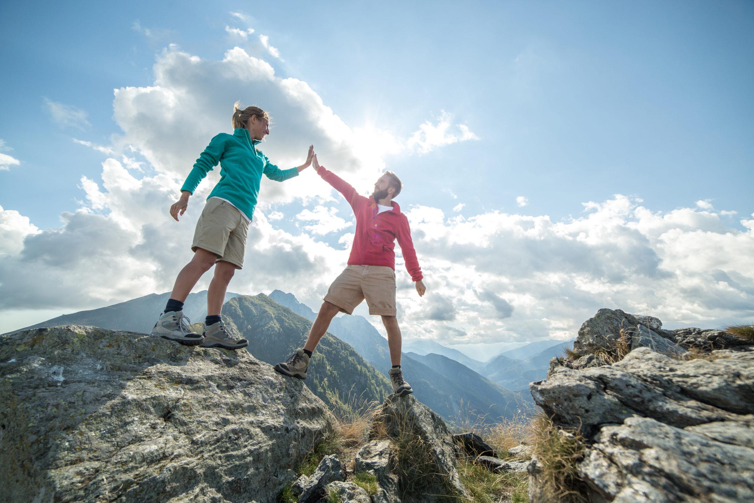 Ein Wanderpaar erreicht feiernd den Gipfel des Berges, high five