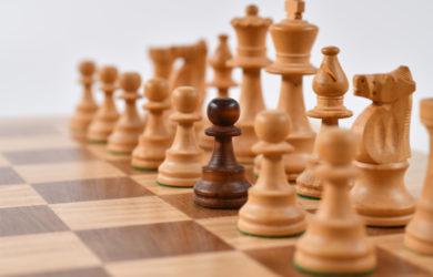 Schachbrett mit einem schwarzen Bauer zwischen weißen Figuren