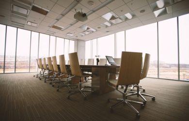 Konferenzraum mit einem großen Tisch und Stühlen mit großen Fenstern