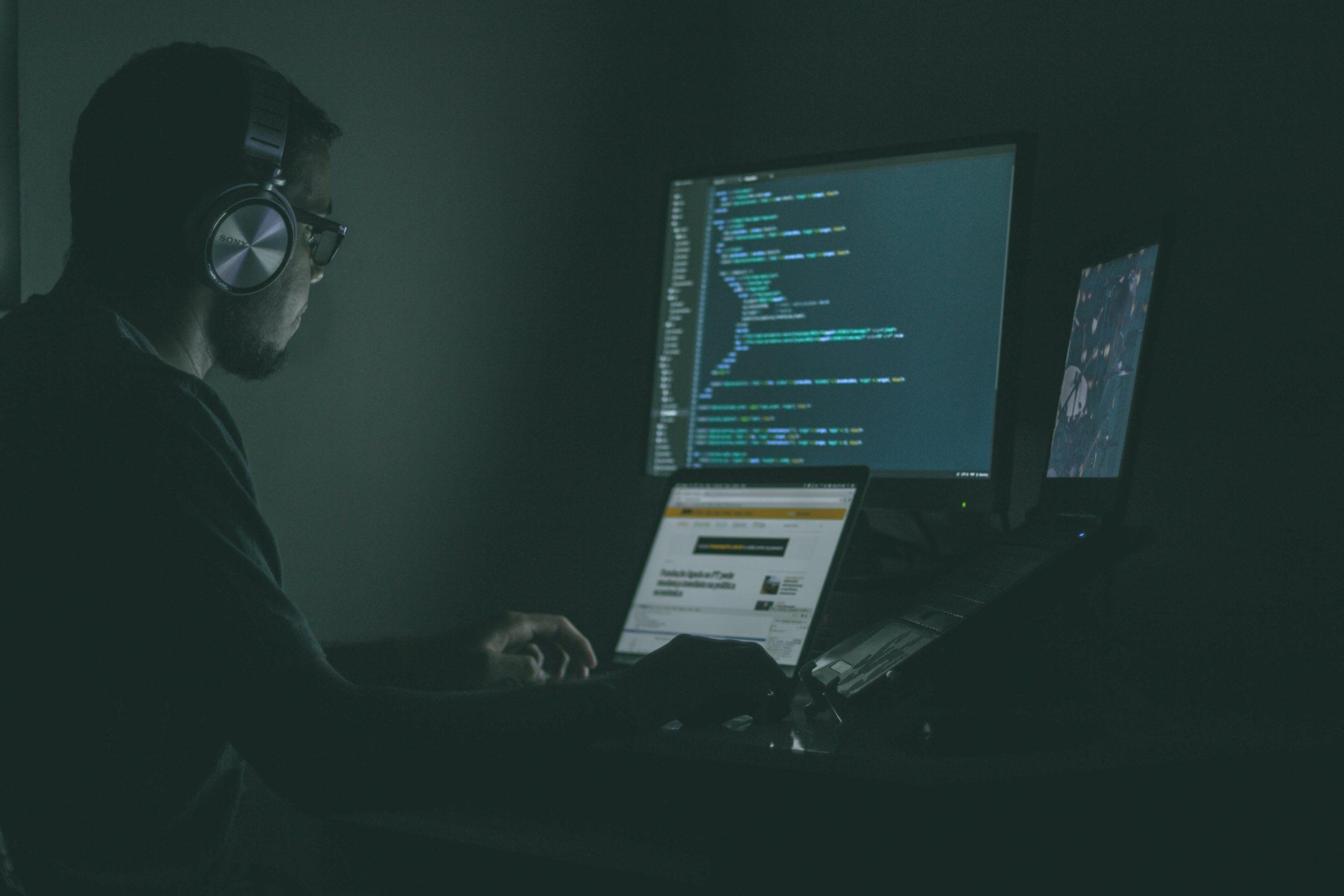 Mann sitz im dunklen Raum und hackt sich in Programme