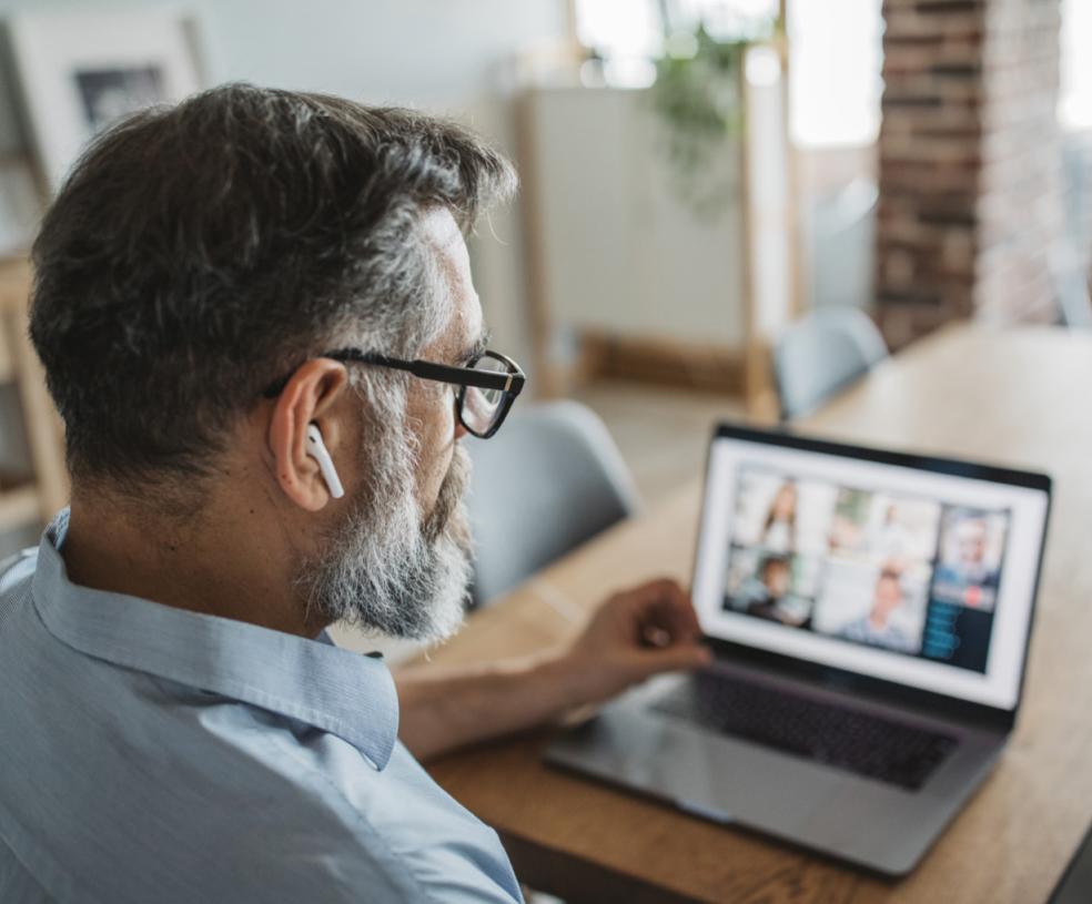 Mann mit Airpods in den Ohren beteiligt sich an einem Online Call im Home Office teilnimmh