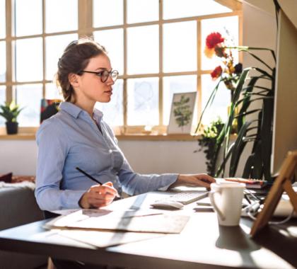 Arbeiterin arbeitet im Home-Office, sitz vor ihrem Computer und schreibt Notizen auf