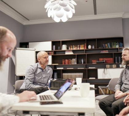 3 Kollegen in einer Besprechung am Arbeitstisch im Büro