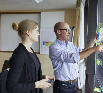 Zwei Kollegen brainstormen Idden auf einer Tafel mit der Hilfe von farbigen Post-It Notes