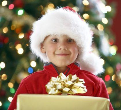 Junge mit Santa Klaus Mütze hält ein Geschenk vor de Weihnachtsbaum