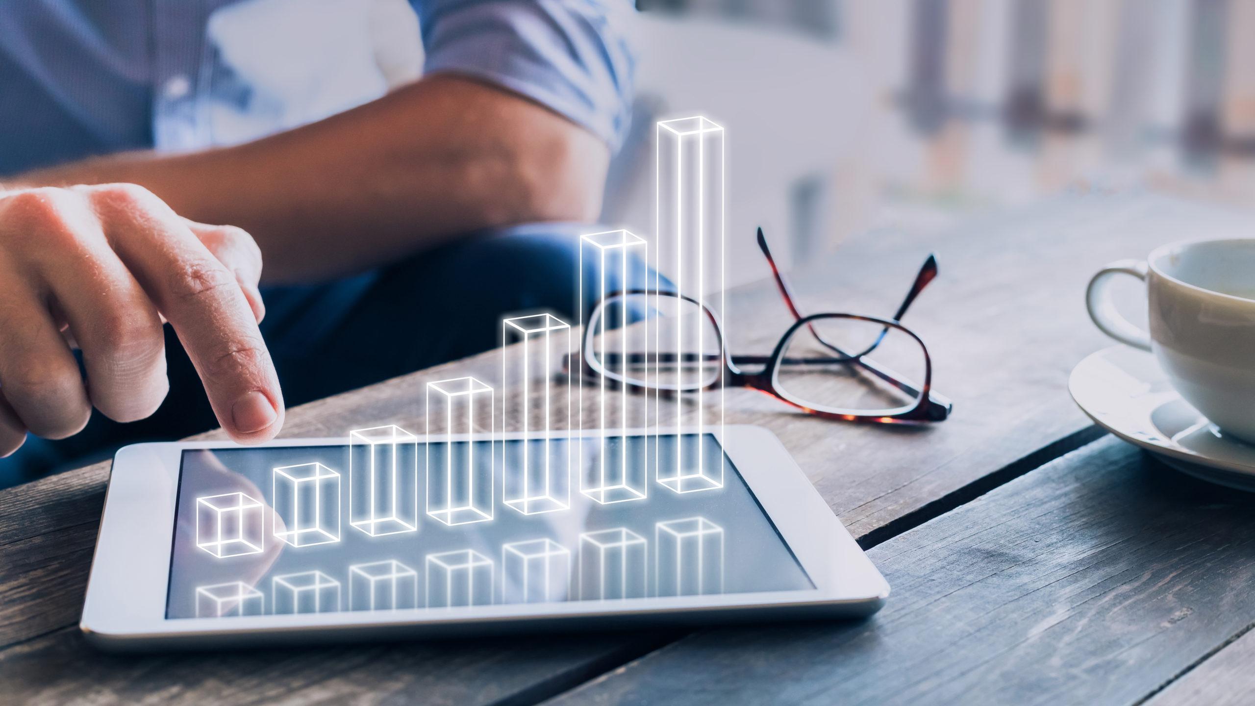 Geschäftsmann, der ein wachsendes 3D-AR-Diagramm analysiert, das über einem digitalen Tablet-Computerbildschirm schwebt und eine erfolgreiche Steigerung des Geschäftsgewinns anzeigt