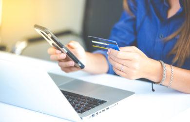 Frau sitzt vor ihrem Laptop mit Ihrem Handy und Kreditkarte in der Hand