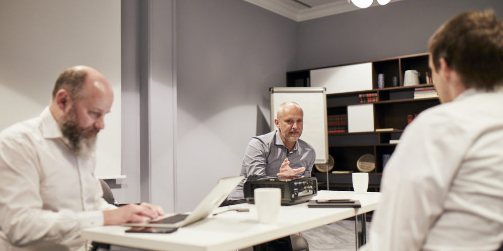 Drei Consileon Mitarbeiter diskutieren.