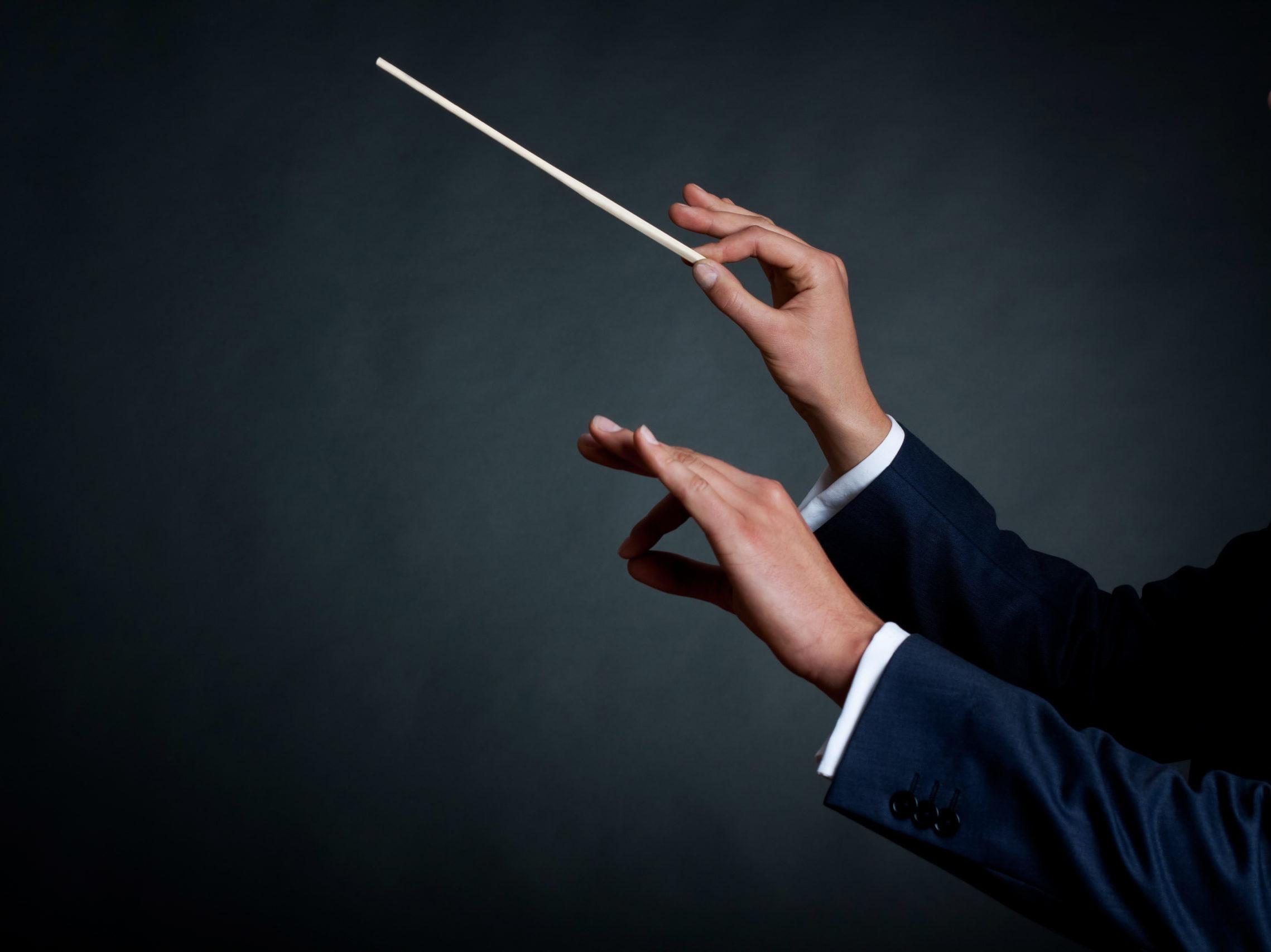 Bild eines männlichen Orchesterdirigenten, der mit seinem Taktstock im Konzert dirigiert