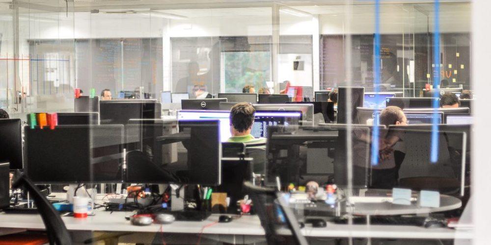 IT-Arbeitsplätze hinter einer Glasscheibe.