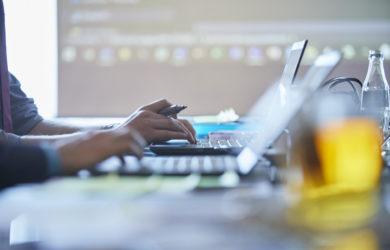 Menschen tippen auf der Laptoptastatur während einer Konferenz