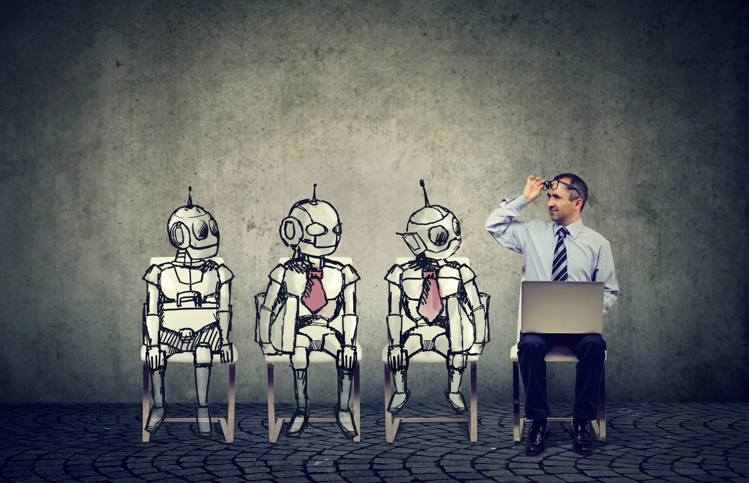 Mensch mit Laptop sitzt verwundert neben 3 RObotern / Ein Mann, der sich um eine Stelle bewirbt, konkurriert mit Cartoon-Robotern, die in der Schlange für ein Vorstellungsgespräch sitzen