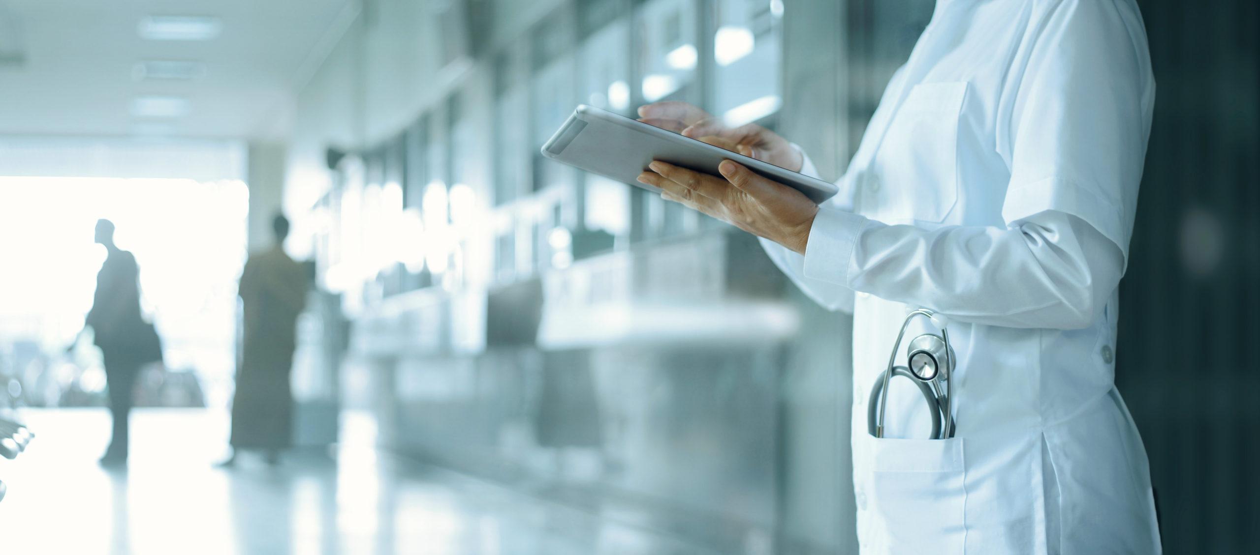 Medizin und Technik. Arzt arbeitet mit einem digitalen Tablett im Krankenhaus