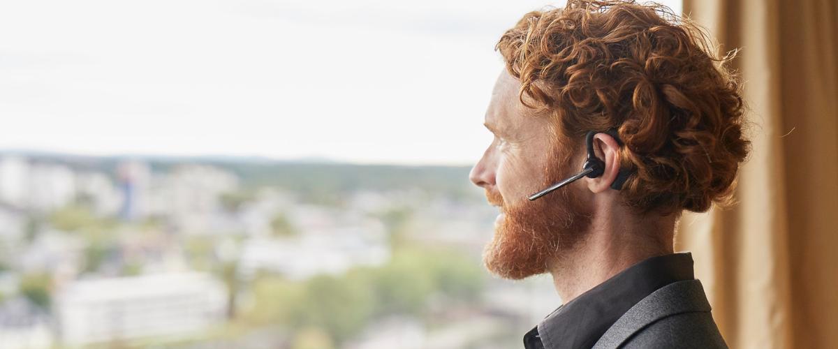 Consultant im Call mit In-Ear Kopfhörern blickt aus dem Fenster raus