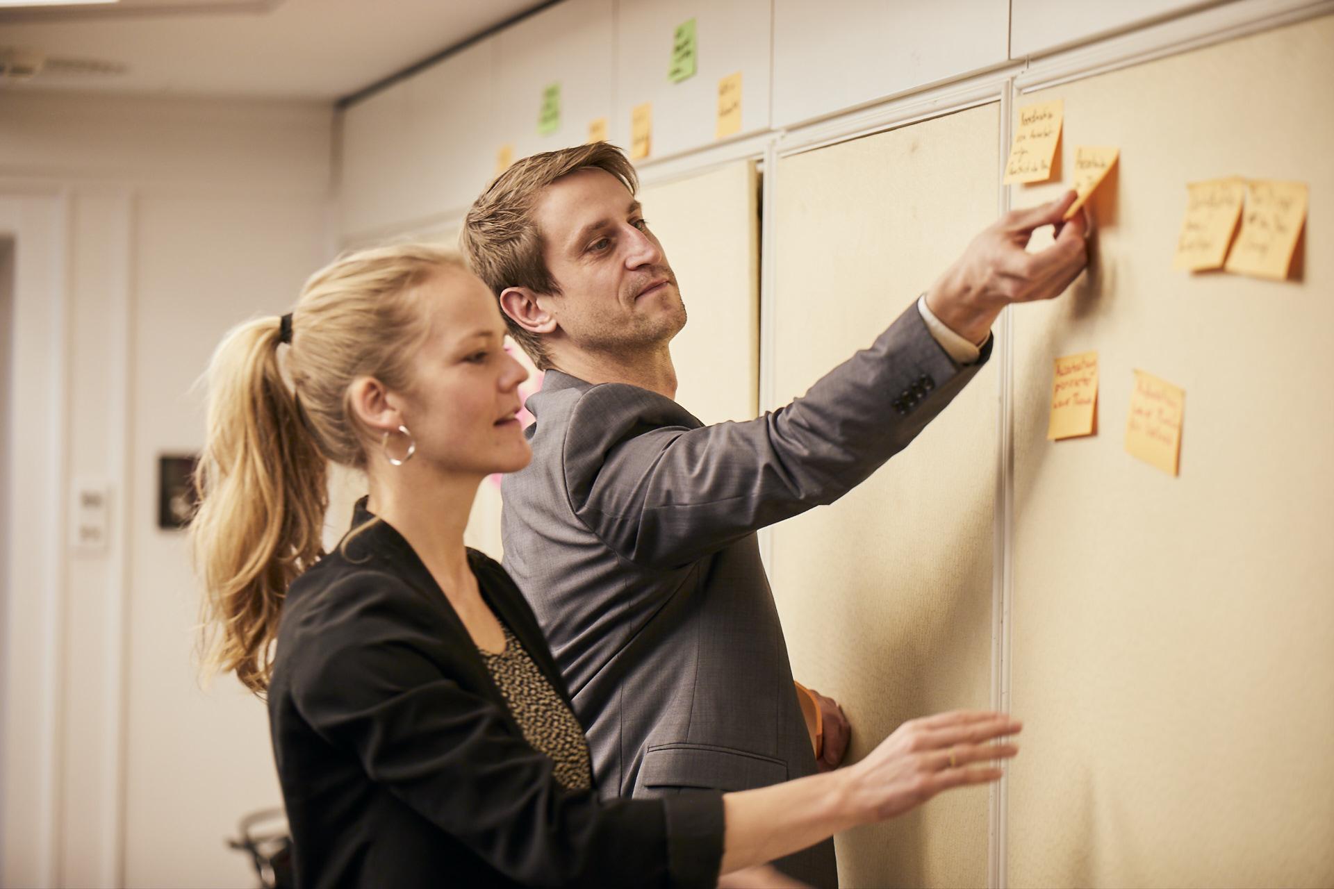 Zwei Kollegen haben eine Brainstorming Session mit farbigen Post-It Notes im Büro