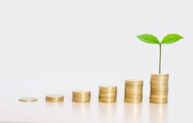 goldenen Münzen gestapelt mit grünen Blättern Wachstum bis auf die obere Münze ESG Environmental Social Governance.