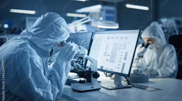 Moderne Fabrik: Ein Team von Ingenieuren und Wissenschaftlern in sterilen Schutzanzügen arbeitet an Desktop-Computern, benutzt Mikroskope und entwickelt Elektronik für die medizinische High-Tech-Forschung