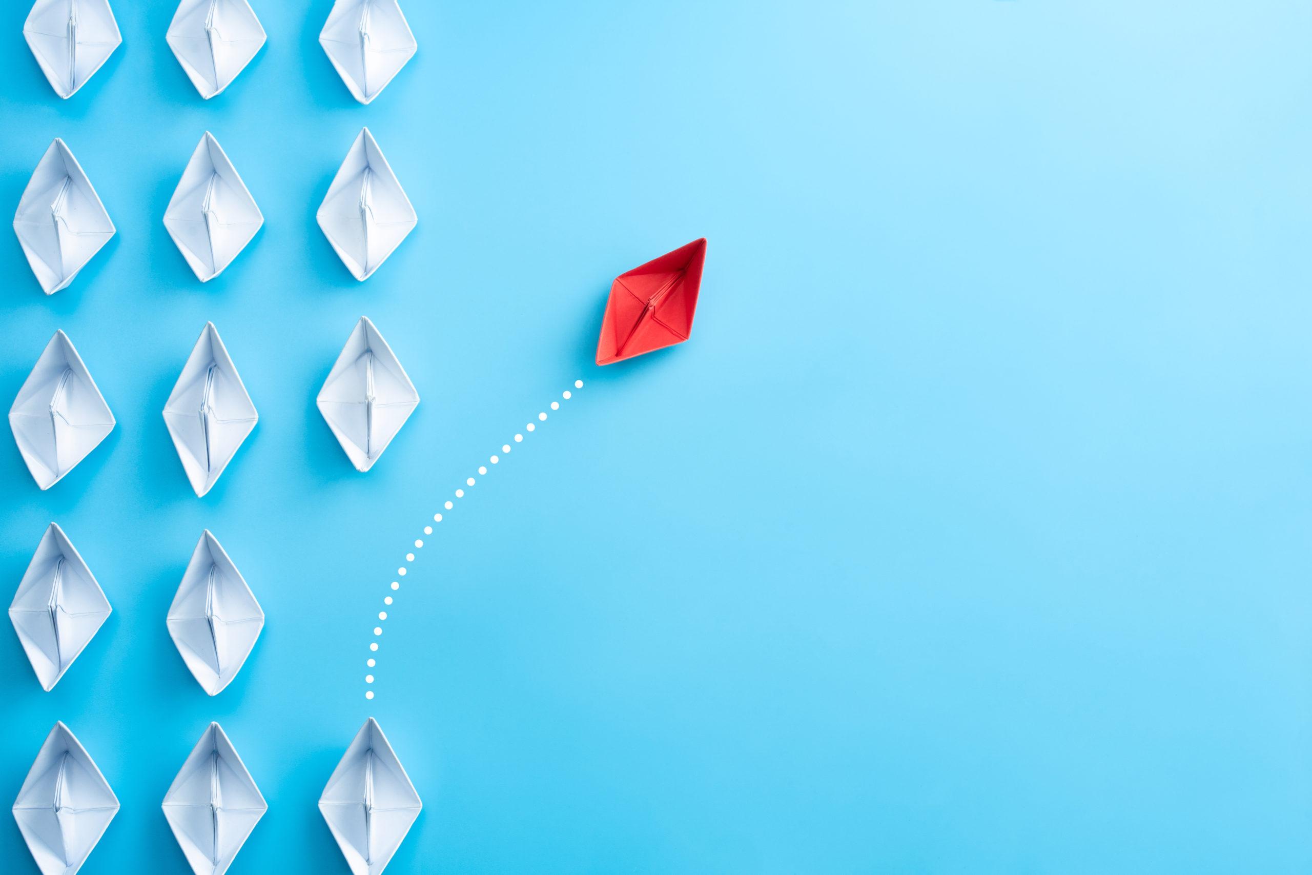 Gruppe von weißem Papier Schiff in eine Richtung und ein rotes Papier Schiff zeigt in verschiedene Richtung auf blauem Hintergrund. / Bild von links angeordneten weißen Papier Schiffen mit einem roten Schiff, der von dem Rest abweicht